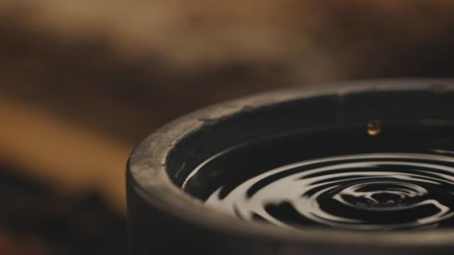 vídeos y material grabado en eventos de stock de caída de café en el contenedor de la fábrica - café negro