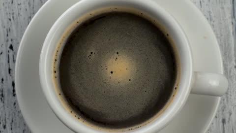vidéos et rushes de mousse café tourbillonne dans la tasse blanche avec du café. shabby fond en bois blanc. top-down vue - en haut
