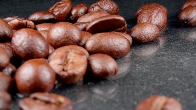 kaffeekörner aus nächster nähe auf grauem hintergrund. - koffeinmolekül stock-videos und b-roll-filmmaterial