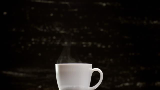kaffee in weiße tasse umgeben von kaffeebohnen auf dunklem hintergrund in 4k uhd - kaffeetasse stock-videos und b-roll-filmmaterial
