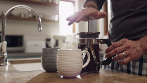 Coffee is always a must 4k video footage of an unrecognizable man making two cups of coffee at home morning stock videos & royalty-free footage
