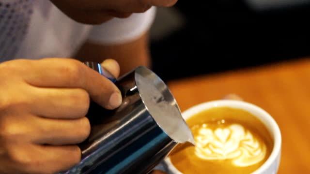 kaffee latte art, milch eingießen von einem barista. - milchkaffee stock-videos und b-roll-filmmaterial