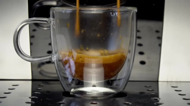 Coffee machine filling a cup with hot  coffee , slow motion