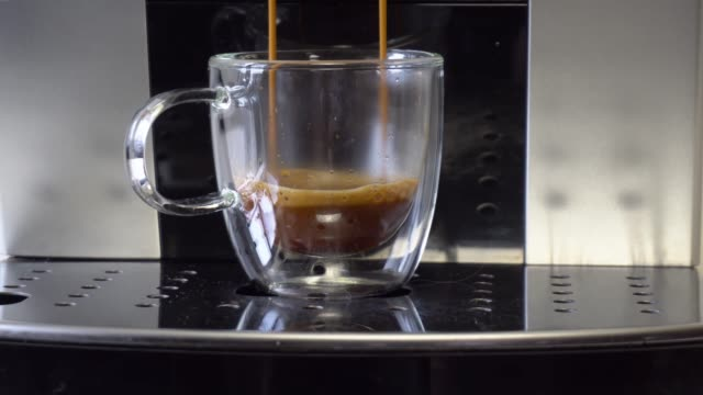 Coffee machine filling a cup with hot  coffee