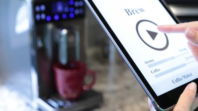 vídeos de stock e filmes b-roll de coffee maker inside smart home being controlled on digital tablet - bluetooth