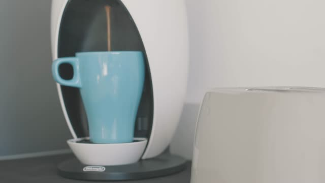 Coffee maker making an espresso with two toasts