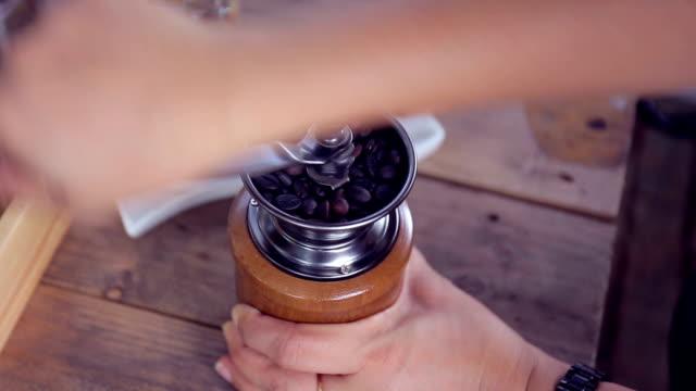 kaffeemühle mahlen der kaffeebohnen. körner von kaffee in einer kaffeemühle. close-up. - geröstete kaffeebohne stock-videos und b-roll-filmmaterial