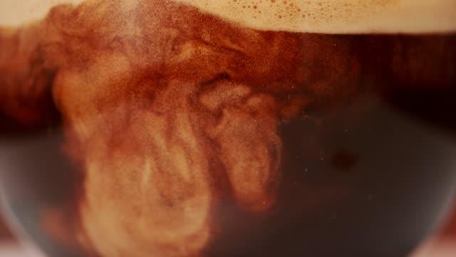 vídeos de stock e filmes b-roll de coffee mixing with milk. super slow motion. - bebida com espuma