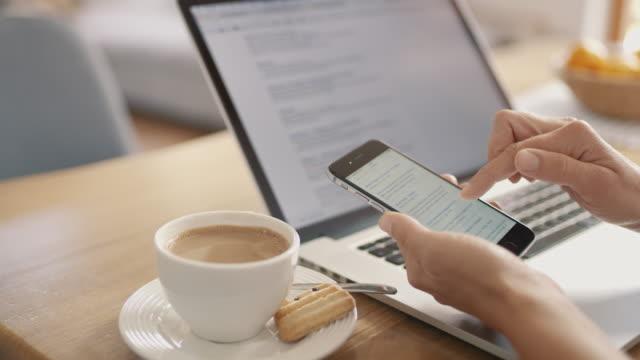 cu kaffe bredvid kvinna använder smart telefon på laptop - skrollning bildbanksvideor och videomaterial från bakom kulisserna