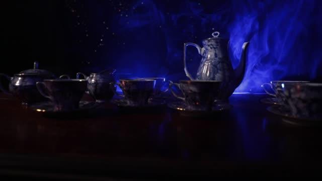 kaffe eller te ceremoni konceptuella tema. gamla vintage keramik te eller kaffekanna med koppar kannan och sugar cup på mörk tonad bakgrund med ljus och rök. tomt utrymme för text. reglaget som sköt - tefat bildbanksvideor och videomaterial från bakom kulisserna