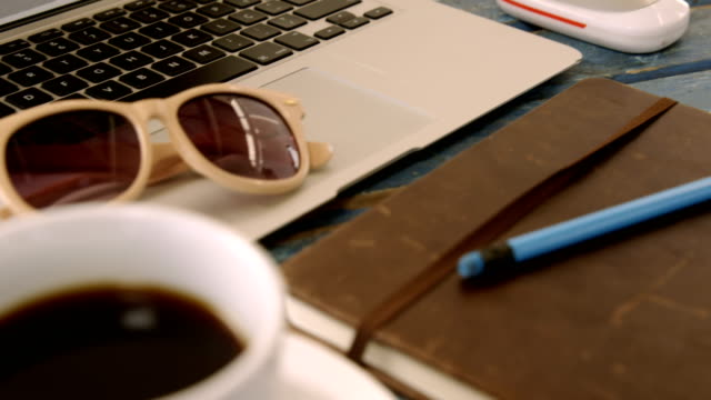 Coffee, organizer, pencil, sunglasses and laptop on table 4k video