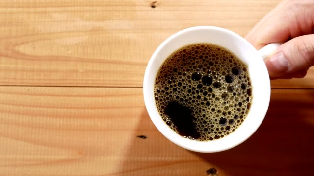 coffee pouring into a cup and hand picking up on wooden table black coffee pouring into a cup and hand picking up on wooden table mug stock videos & royalty-free footage