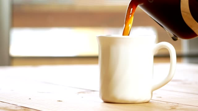 vídeos de stock e filmes b-roll de coffee pouring into a white cup and hand stirring the coffee on wooden table - coffee table