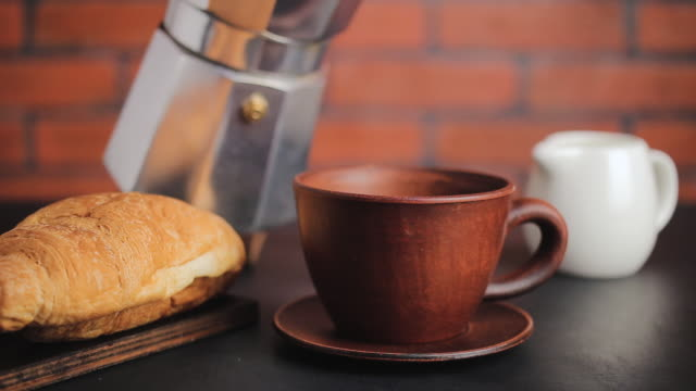 Coffee pouring into brown clay cup from moka pot, making breakfast, brick wall background