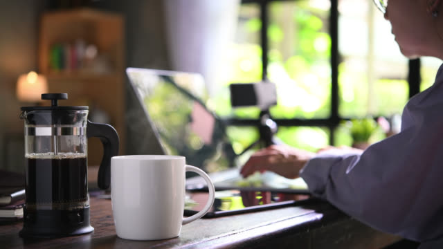 vidéos et rushes de une presse à café et une tasse sur un bureau de travail avec une personne travaillant de la maison - pots de bureau