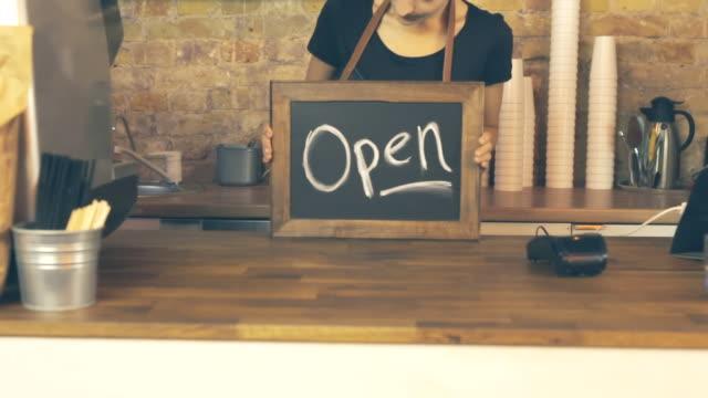 a coffee shop worker holds a open sign. - modella negozio video stock e b–roll