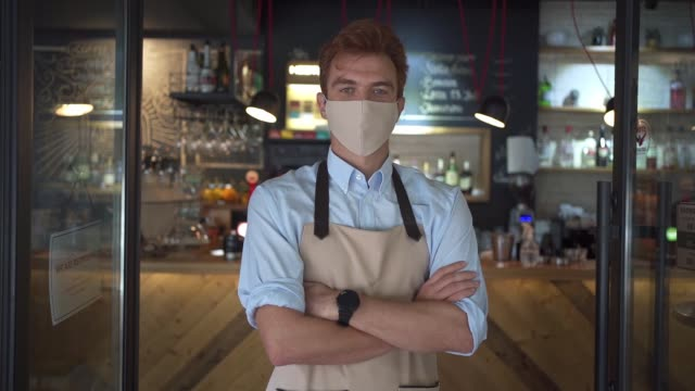 Coffee shop worker wearing PPE while standing in front of coffee shop