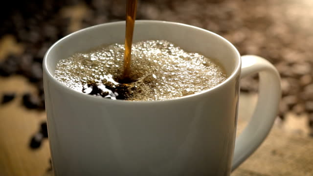 kaffee zeitlupe pour makro mit kaffeebohnen - kaffeetasse stock-videos und b-roll-filmmaterial