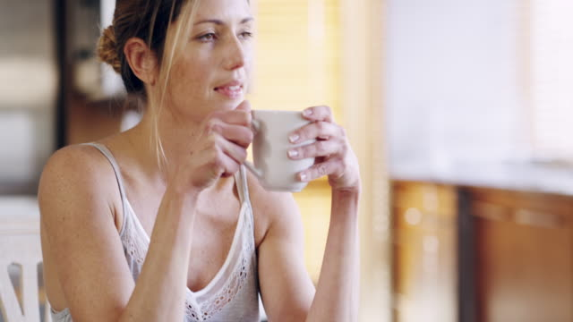 Coffee soothes my soul 4k video footage of a mature woman enjoying a cup of coffee at home mug stock videos & royalty-free footage