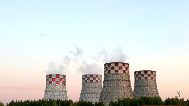 Cogeneration power plant in city. Thermal Power Station chimney smoke sky. Sunset landscape. Combined heat and power plant near megapolis. Chimney-stalk and ecology problem on Earth. Heat electricity. video