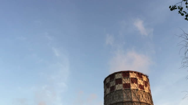 Cogeneration power plant in city. Tilting down from blue sky to pipes tubes chimney-stalk. Thermal Power Station chimney smoke sky. Sunset landscape. Combined heat and power plant near megapolis. video