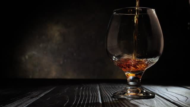 il cognac viene versato in un bicchiere. su sfondo scuro. 4k. - brandy video stock e b–roll