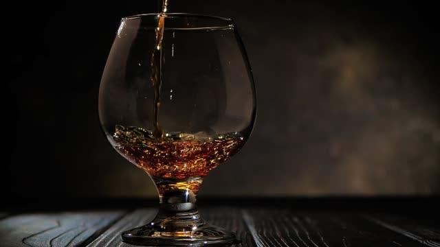 il cognac viene versato in un bicchiere. su sfondo scuro. - rum superalcolico video stock e b–roll