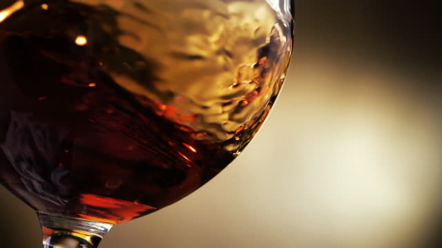 cognac is rotated in a glass. on dark background. - rum superalcolico video stock e b–roll