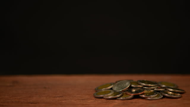 Coin falling to glass bottle on black background .Busisnes , save money,spend money ,economic concept.4k stop motion.Reverse directon.