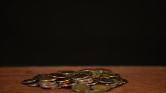 Coin falling to glass bottle on black background .Busisnes , save money,spend money ,economic concept.4k stop motion.
