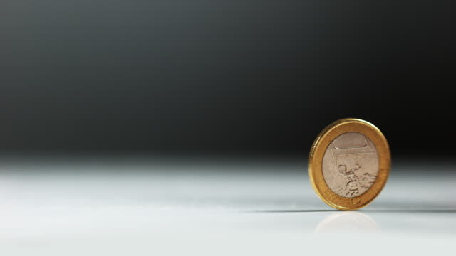 Coin of 1 Euro Rolling against White Background, Slow motion 4K