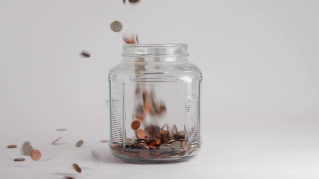 Coins Fall into Clear Jar in Slow Motion a clear jar fills up with coins dropped from above, spilling and filling the jar in slow motion. jar stock videos & royalty-free footage
