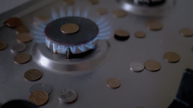 Coins Fall on Gas Burner, which Glowing with a Blue Flame in the Kitchen. 180 fps