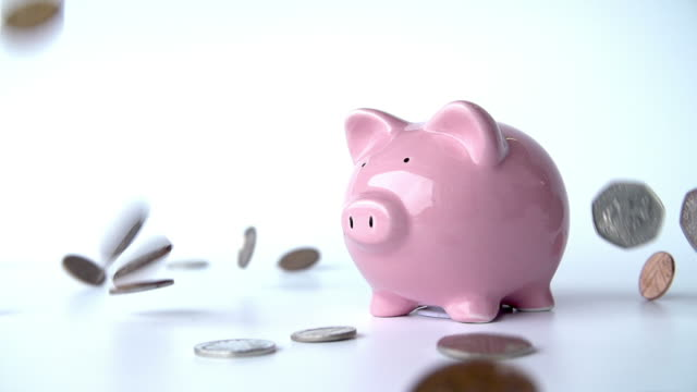 Coins Falling Around Piggy Bank In Slow Motion Slow motion sequence of coins falling around pink ceramic piggy bank.Shot on Sony FS700 at frame rate of 50fps piggy bank stock videos & royalty-free footage