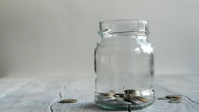 mynt falla i burken. besparingar i burken - lön bildbanksvideor och videomaterial från bakom kulisserna