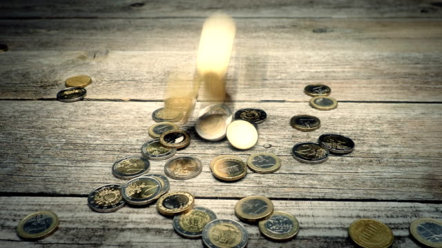 Coins falling on wooden background - 4K VIDEO