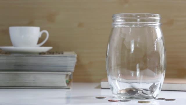 vidéos et rushes de pièces de monnaie dans un bocal en verre sur la table. pièces de monnaie tombent dans un bocal. - pots de bureau