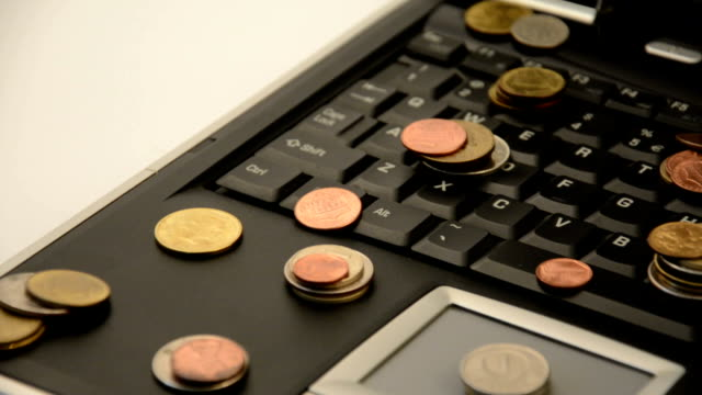 Coins on a laptop isolated on white background