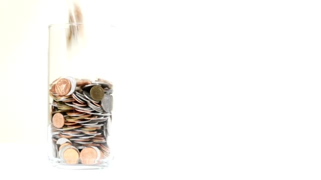 münzen gießen in glas auf weißem hintergrund - konzept geld sparen - amerikanische geldmünze stock-videos und b-roll-filmmaterial