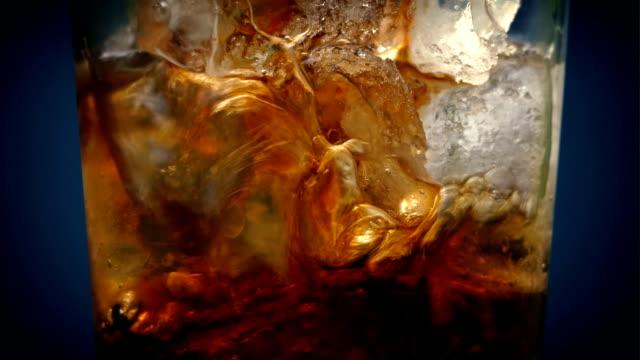 vídeos de stock, filmes e b-roll de coca derramada sobre cubos de gelo tiro macro - refrigerante