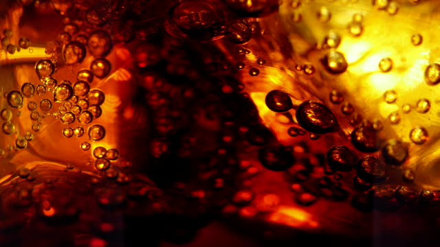 Cola and ice in glass. Cola pouring into a glass with ice cubes. Сlose-up cola stock videos & royalty-free footage