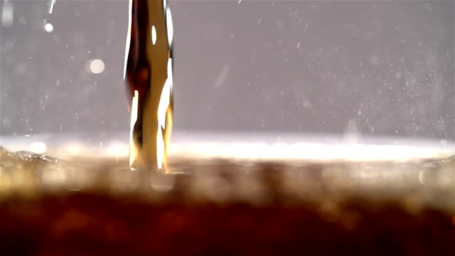 Cola carbonated drink pouring in glass with splash. Slow motion Pouring Coca cola and making splashes on black background shooting with high speed camera soda stock videos & royalty-free footage
