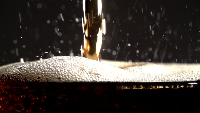 Cola carbonated drink pouring in glass with splash. Slow motion video
