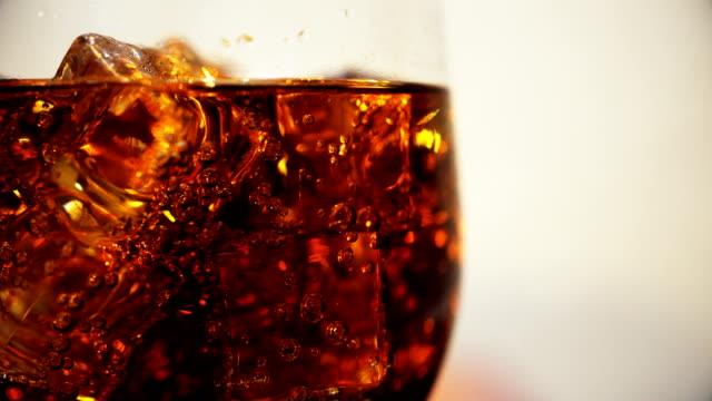 vídeos y material grabado en eventos de stock de cola en el vaso con cubos de hielo y burbujas girando. fondo de alimentos. primer plano de la soda. - cola gaseosa