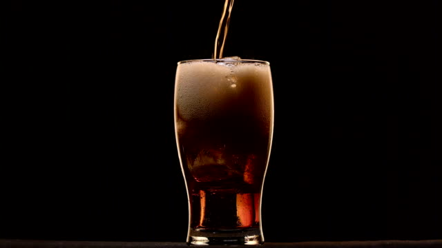 Cola poured into a glass with ice it foams to form a foam cap. Black background Cola poured into a glass with ice it foams to form a foam cap poured over the edge. Black background soda stock videos & royalty-free footage