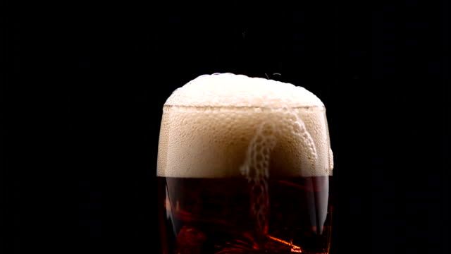 Cola pouring into glass with ice cubes and it overflows with foam flowing over the edge. Black background. Close up Cola pouring into glass with ice cubes and it effervescent foam overflows with flowing over the edge. Black background. Close up cola stock videos & royalty-free footage