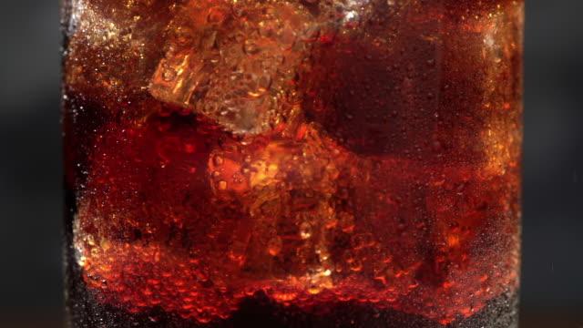 vídeos de stock e filmes b-roll de cola soda drink bubbles in glass with ice cubes, macro footage, close up - bebida fresca