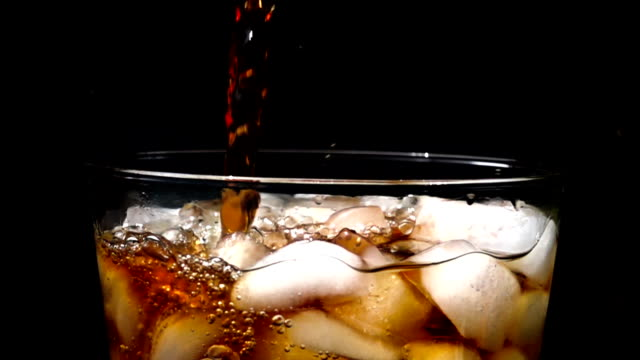 Cola soda pouring into glass of ice with splashes at slow motion on a black background Pouring cola soda at slow motion into glass of ice with splashes on black background. soda stock videos & royalty-free footage