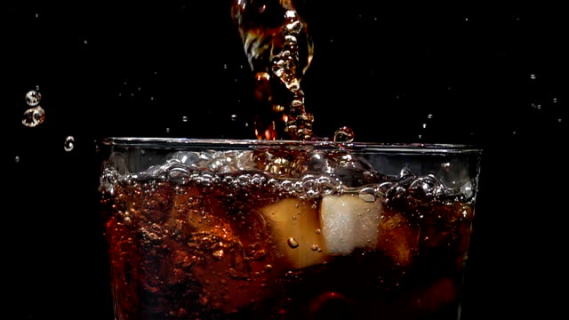Cola soda pouring into glass of ice with splashes at slow motion on a black background Pouring cola soda at slow motion into glass of ice with splashes on a black background. soda stock videos & royalty-free footage