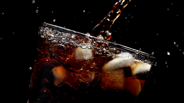pouring cola soda into glass of ice with splashes at slow motion on a black background - soda pop stock videos and b-roll footage